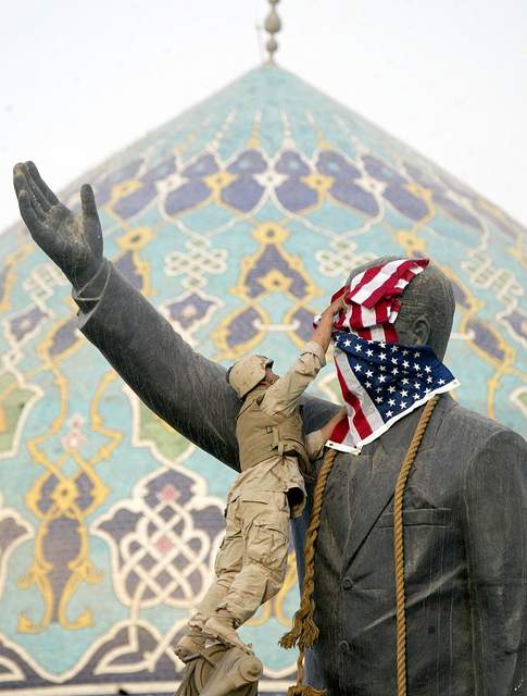 Cpl Edward Chin from New York of the 3rd battalion, 4th Marines regiment, set up the star and stripes flag on the face of Iraqi President Saddam Hussein's statue  before to tear down it,  in downtown Bagdad, Wednesday, April 9, 2003. (AP Photo/Laurent Rebours)